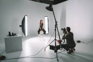professional photographer and beautiful model on fashion shoot in photo studio with lighting equipment